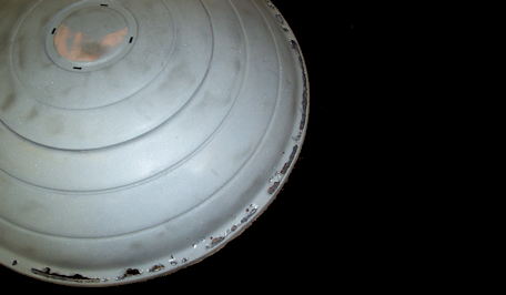 Cadillac hubcap before restoration